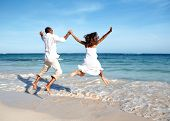 Happy couple jumping on beach. Summer vacation.