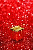 Small decorative gift box on shiny glitter background