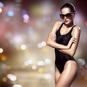 Fashion woman. Bikini and sunglasses. Night city background.