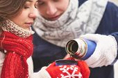 Young couple going to drink hot tea on winter day