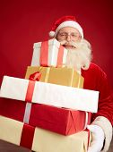 Generous Santa with pile of Christmas presents