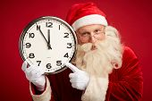 Cheerful Santa pointing at clock in his hand and looking at camera