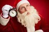Pensive Santa with alarm clock showing five minutes to xmas by his ear