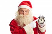Santa pointing at alarm clock showing five minutes to xmas