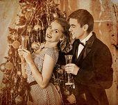 Couple on party near Christmas tree. Sepia toned.