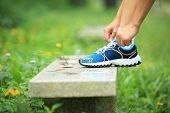 woman tying shoelace outdoor