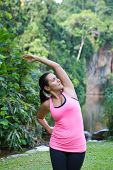 Sporty woman stretching left side of body after exercising in outdoor park