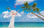 young beautiful bride on the wedding day with wedding bouquet on tropical sea and beach background