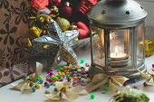 Christmas still life: lantern with burning candle and New Year tree decorations. Aperture 4