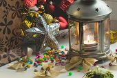 Christmas still life: lantern with burning candle and New Year tree decorations. Aperture 8