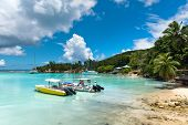 LA DIGUE, SEYCHELLES - 21 OCTOBER 2014 - Small boats in the harbor at La Digue, Seychelles , moored alongside the golden sand of a tranquil tropical beach in a sheltered lagoon on 21 October 2014