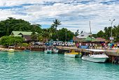 MAHE, SEYCHELLES - 21 OCTOBER 2014 - People walking on the quay at La Digue harbor in the Seychelles with several pleasure boats moored alongside on 21 October 2014