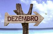December (In Portuguese) sign with a beach on background