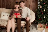 Young man and woman sits near christmas tree