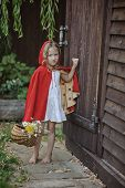 Cute blonde girl playing little red riding hood in the garden