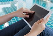 Woman working with tablet sitting at swimming pool