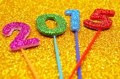 glittering numbers of different colors forming the number 2015, as the new year, on a shiny golden background