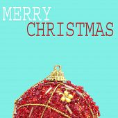 an ornamented red christmas ball and the sentence merry christmas on a blue background with a pop art style