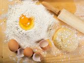 Baking preparation: eggs flour rolling pin on a board