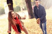 A picture of a happy couple having fun in the park in autumn