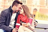 A picture of a young romantic couple kissing on a bench with smartphone in the park