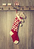 Christmas stocking filled with teddy bear and train set on ledge