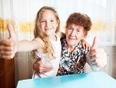 Senior with girl. Generation. Elderly woman with great-grandchild showing sign ok