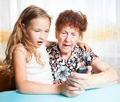 Senior with girl. Generation. Elderly woman with great-grandchild looking at mobile phone