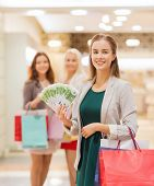 sale, consumerism and people concept - happy young women with shopping bags and euro cash money in mall