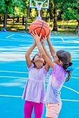 Seven year old girls  playing basketball