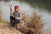 Cute child girl in knitted hat and sweater playing on river side
