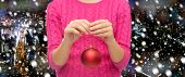 christmas, decoration, holidays and people concept - close up of woman in pink sweater holding christmas ball over snowy night city background