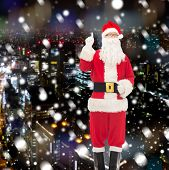 christmas, holidays, gesture and people concept - man in costume of santa claus pointing finger up over snowy night city background
