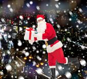 christmas, holidays and people concept - man in costume of santa claus running with gift box over snowy night city background
