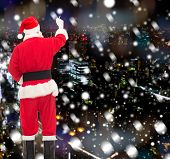 christmas, holidays and people concept - man in costume of santa claus writing something from back over snowy night city background