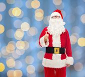 christmas, holidays, gesture and people concept- man in costume of santa claus showing thumbs up over blue lights background