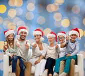 family, happiness, generation, holidays and people concept - happy family in santa helper hats sitting on couch and showing thumbs up gesture over blue lights background