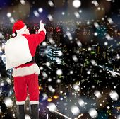 christmas, holidays and people concept - man in costume of santa claus with bag pointing finger from back over yellow lights background over snowy night city background
