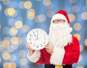 christmas, holidays and people concept - man in costume of santa claus with clock showing twelve over blue lights background