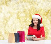 christmas, holidays, technology and people concept - smiling woman in santa helper hat with shopping bags and tablet pc computer over yellow lights background