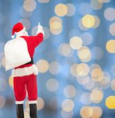christmas, holidays and people concept - man in costume of santa claus with bag pointing finger from back over yellow lights background over blue lights background