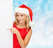 winter holidays, christmas, advertising and people concept - smiling young woman in santa helper hat with white blank billboard over blue lights background