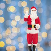 christmas, holidays, gesture and people concept - man in costume of santa claus pointing finger up over blue lights background