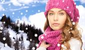 happiness, winter holidays, christmas and people concept - close up of young woman in pink hat and scarf over snowy mountains background