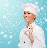 christmas, cooking, profession, gesture and people concept - smiling female chef showing ok hand sign over blue snowy background