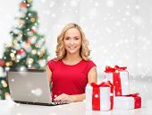 technology, holidays, online shopping and people concept - woman with gift boxes and laptop computer over living room background