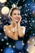 people, holidays, royalty and glamour concept - smiling woman in evening dress wearing golden crown over night lights and snow background
