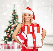 holidays, celebration and people concept - smiling woman in santa helper hat and red dress with gift boxes over living room and christmas tree background