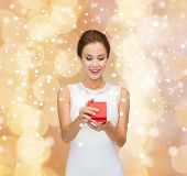 holidays, presents, wedding and happiness concept - smiling woman in white dress holding red gift box over beige lights background and snow