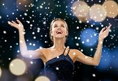 people, happiness, holidays and glamour concept - laughing woman rising hands and looking up over night lights and snow background